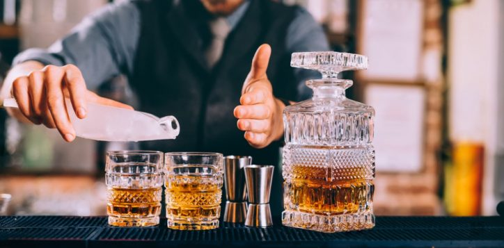 stock-photo-close-up-of-barman-hands-adding-ice-and-whiskey-to-modern-urban-cocktails-sky-bar-serving-elegant-764280106