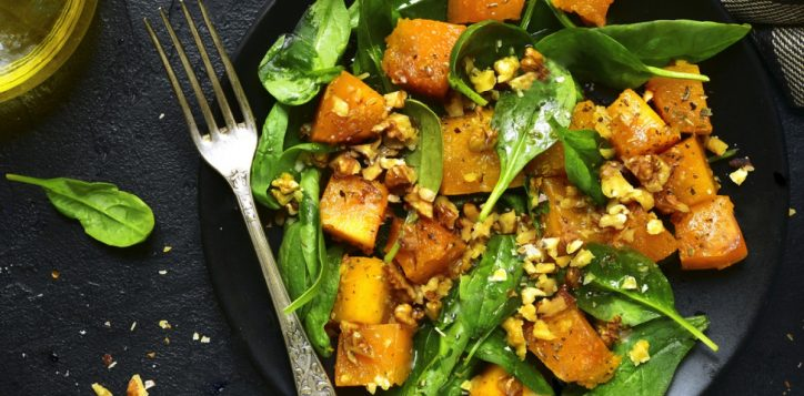 stock-photo-roasted-pumpkin-salad-with-spinach-and-walnut-on-a-black-plate-on-a-stone-background-top-view-496234729