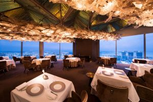 the interior of Jaan Restaurants, with white draped tables under a massive chandelier