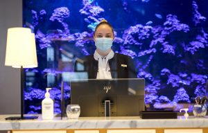 Front office attendant wearing face mask as part of ALLSAFE / Covid-safe procedure
